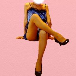 青いテカテカのミニドレスで脚を組んで座っている