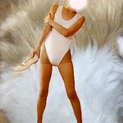 毛皮のようなフカフカを背景に白いレオタードでシューズを持って立っている