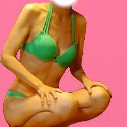緑色のビキニで膝に手をついて座っている