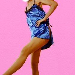 青いテカテカのミニドレスで片足を斜めに少しだけ上げて立っている