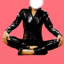 全身黒のボンテージスーツで胡坐をかいて正面向きで座っている