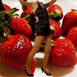 苺をバックに黒いチャイニーズドレスを着ている