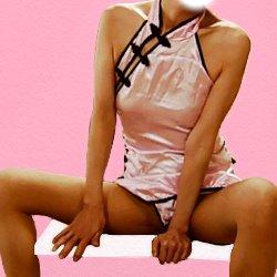 ピンクのチャイニーズドレスでお股を開いて机に座っている