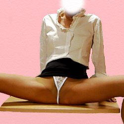 白いブラウスに黒のミニで大股を開いて机に上に座っている