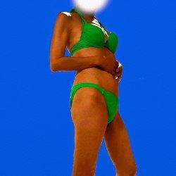 緑色のビキニで青を背景に立っている