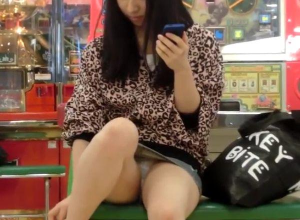 ゲーセンでおまたゆるゆるでスマホを操作する女の子を隠し撮り