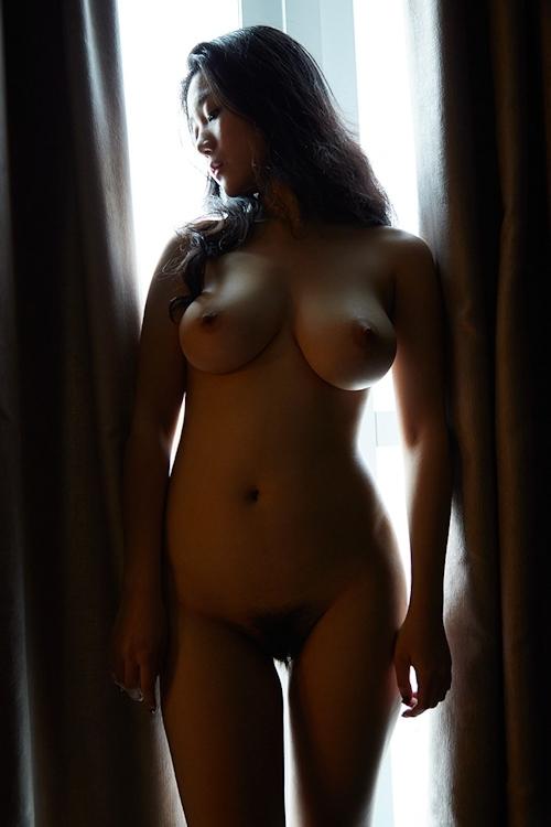 暗闇に照らされた巨乳女性のヌード画像 2