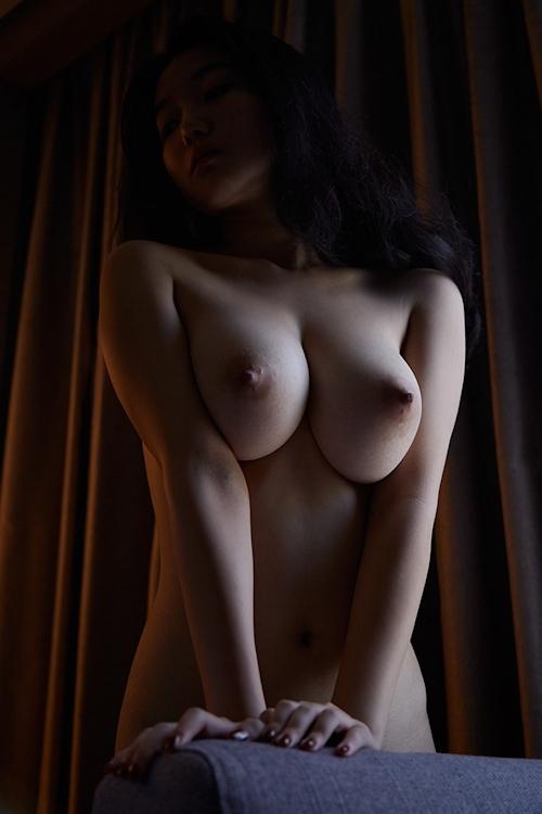 暗闇に照らされた巨乳女性のヌード画像 3