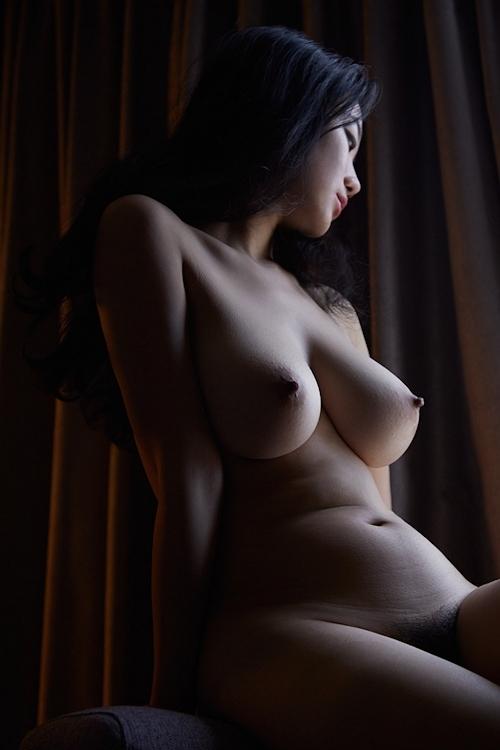 暗闇に照らされた巨乳女性のヌード画像 5