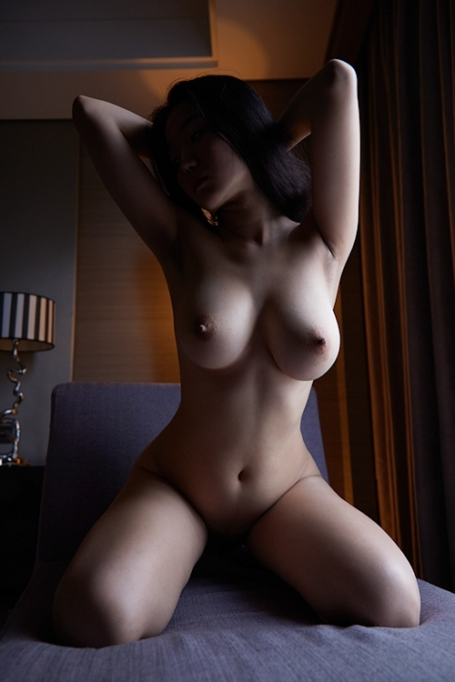 暗闇に照らされた巨乳女性のヌード画像 7