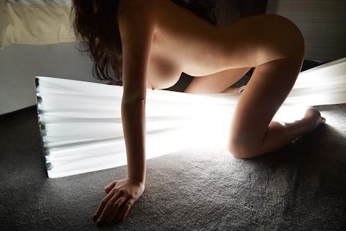 暗闇に照らされた巨乳女性のヌード画像 8